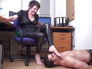 foot slave of mature dominatrix in home office